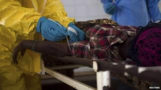 Medical staff take a blood sample from a suspected Ebola patient at the government hospital in Kenema, Sierra Leone, 10 July, 2014.