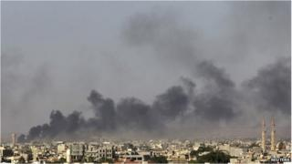 Black smoke after clashes between militants and government forces in Benghazi on 26 July.