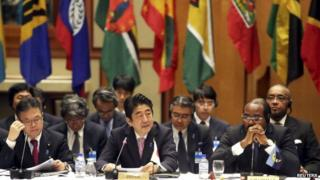 "Japan""s Prime Minister Shinzo Abe (C) addresses the Caribbean Community (Caricom)/Japan summit next to Caricom chairman and Prime Minister of Antigua and Barbuda Gaston Browne (R) and Japan""s Deputy Chief Cabinet secretary Hiroshige Seko, in Port-of-Spain July 28, 2014"