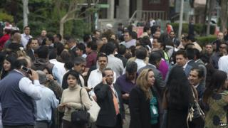 People stand outside their office building in Mexico City after an earthquake on 8 May 2014
