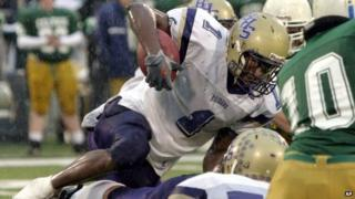 Bloomington High School running back Adrian Arrington tries to clear a pile of Providence Catholic defenders during the Class 6A championship football game in Champaign, Illinois 27 November 2004