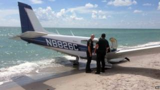 Photo provided by the Sarasota County Sheriff's Office shows emergency personnel at the scene of a small plane crash in Caspersen Beach in Venice, Florida 27 July 2014