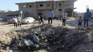 People look at the wreckage of a government MiG warplane which crashed during Tuesday's fighting, in Benghazi, Libya, 29 July 2014