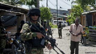 A man walks by Colombian marines patrolling during security operations in Buenaventura on 25 March, 2014.