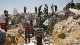 Palestinian rescue workers search for victims in the rubble of a building destroyed by an Israeli air strike