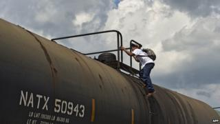 A Central American migrant gets on La Bestia cargo train in Apizaco on 22 July, 2014