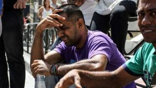 An immigrant cries as he takes part in a demonstration outside court in the city of Patras
