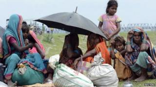 Villagers with their belongings sit in a relief camp after their evacuation at Supaul district in the eastern Indian state of Bihar August 3, 2014.