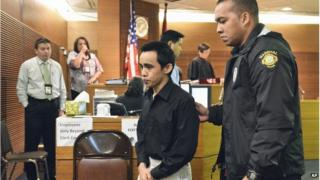 Suspect Chad DeSoto (centre) is escorted from a Superior Court of Guam courtroom during a midday break on Monday, 23 June, 2014, in Hagatna, Guam