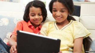 Indian girls play with a tablet