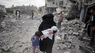 A Palestinian woman passes by rescuers inspecting the rubble of destroyed houses