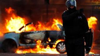 Police officer and burning car during riots of August, 2011