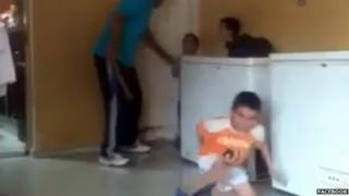 Still of the video showing a Egyptian man beating young orphans