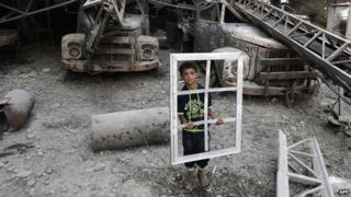 A Palestinian youth holds a window frame as he inspects a destroyed building in the Al-Shejaea neighbourhood of Gaza City