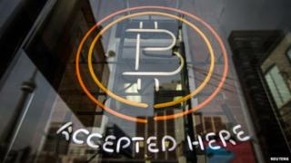 "A sign reads ""Bitcoin accepted here"""