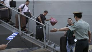 Chinese nationals evacuated from Libya carry their baggage after arriving at the port of Piraeus, near Athens, Greece (2 August 2014)