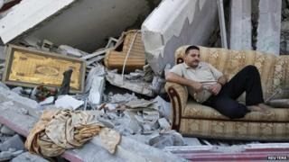 A Palestinian sits amid the ruins of destroyed homes in the Shejaia neighbourhood in Gaza City (6 August 2014)