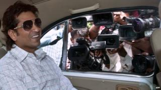 Indian cricketer Sachin Tendulkar smiles as he arrives at Parliament House in New Delhi, July 2012