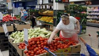 A woman chooses tomatoes in a supermarket in Moscow