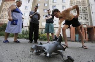 Residents examine a shell fragment in Donetsk, 8 August