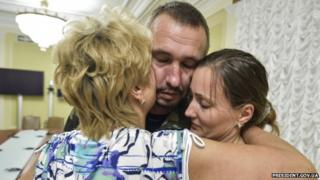 Capt Roman Zasukha hugging mother and wife after release