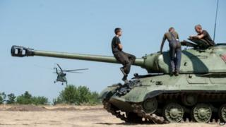 Ukrainian government soldiers sit atop of a tank in Donetsk region, eastern Ukraine, Saturday, Aug. 9