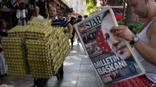 "A man reads a newspaper in central Istanbul, Turkey, with a front page headline reading ""President of the Nation"""