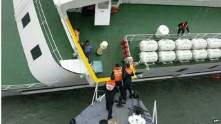 Coast guard officers rescue passengers from the deck of the Sewol