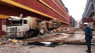 Picture of a lorries destroyed by parts of a building damaged by a quake and its aftershocks, in Iquique.