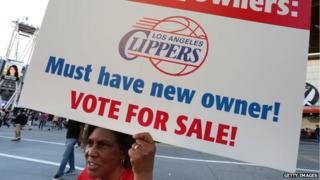 Susan Wright holds a sign protesting racist comments made by L.A. Clippers owner Donald Sterling outside Staples Center before a playoff game 29 April 2014