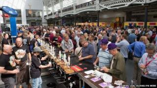 Attendees enjoying and tasting different types of beer at the Great British Beer Festival