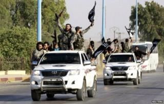 Islamic State fighters wave flags as they drive through Raqqa province - 30 June 2014