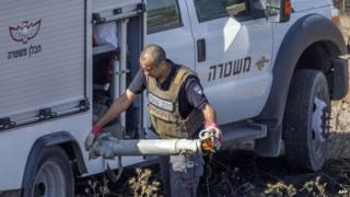 Israeli bomb disposal expert collects remains of rocket fired by Gaza militants 29/07/2014