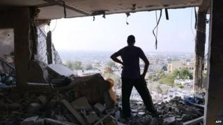 Palestinian man in rubble of apartment complex, Gaza