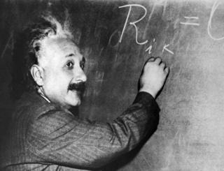 Albert Einstein writing an equation on a blackboard