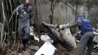 Air force members survey the wreckage site of the crashed private jet, August 14, 2014.
