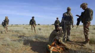 French soldiers stand next to a nomad in desert between Timbuktu and Gao on 30 October 2013
