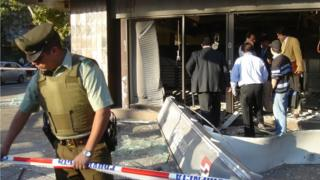 Police cordon off a bank in Santiago where a home-made explosive device went off