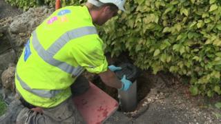 Workman installing water meter in road