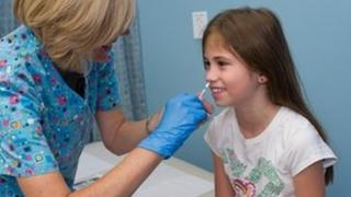 Girl being given flu vaccine nasally