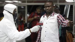 A Nigerian port health official uses a thermometer on a worker at the arrivals hall of Murtala Muhammed International Airport in Lagos, Nigeria, Wednesday, Aug. 6, 2014.