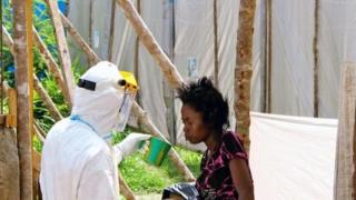 A health worker offers water to a woman with Ebola in Kenema, Sierra Leone, in July 2014.