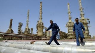 A file picture taken on May 2003 shows workers walking at Iraq's largest refinery complex in Baiji