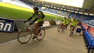 Cyclists inside the King Power Stadium