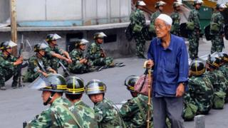 An Uighur man walks past soldiers