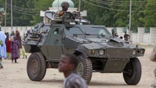 In this file photo taken Thursday, Aug. 8, 2013, a Nigerian soldier patrols in an armoured car, during Eid al-Fitr celebrations, in Maiduguri, Nigeria.