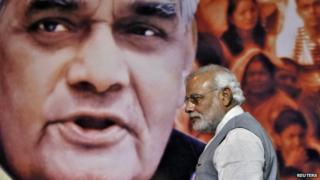 Indian Prime Minister Narendra Modi walks in front of a picture of former Indian Prime Minister Atal Behari Vajpayee after a news conference in New Delhi July 9, 2014.