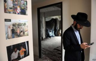 A rabbi stands alongside photographs of Rabbi Gavriel Holtzberg at Nariman (Chabad) House in the Indian city of Mumbai on August 26, 2014