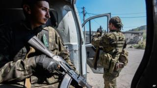 Pro-Russian rebels stand guard at the vehicle used for transportation of mobile military groups in Petrovskiy district in the town of Donetsk, eastern Ukraine