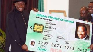Nigerian President Goodluck Jonathan holds a replica of his electronic identity card - 28 August 2014